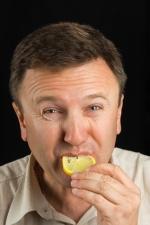 Mann beißt in eine Zitronenscheibe