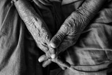 Hände einer alten Frau gefaltet im Schoß